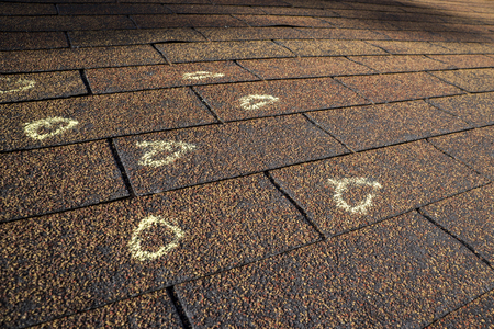 Insurance Adjuster marked hail damage on a insureds roof.