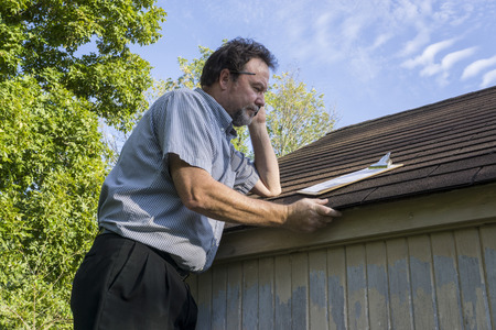 Insurance adjuster checking a insureds roof foe hail damage. Foto de archivo
