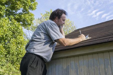 Insuance 조정자는 보험 지붕에 수리 비용을 계산하는 휴대 전화에. 스톡 콘텐츠