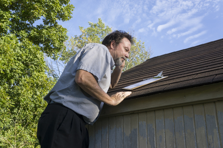 Insurance adjuster on cell phone while looking for hail damage.