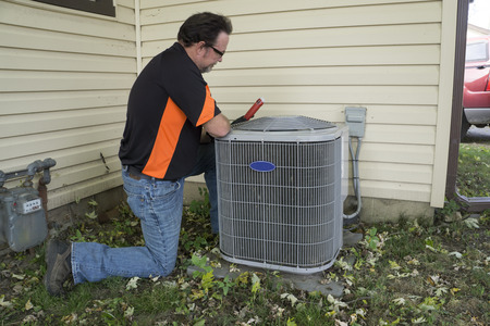 air: Repairman checking outside air conditioning unit  for voltage.