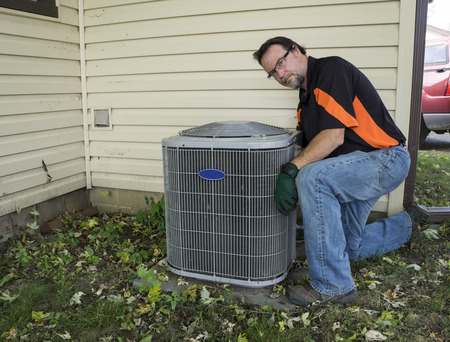 air: Repairman cleaning outside air conditioner unit grill.