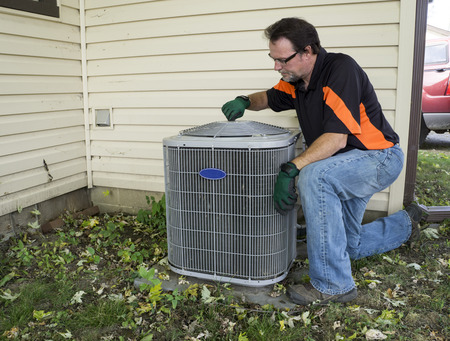 man in air: Repairman tightening fan shroud on outside air conditioning unit