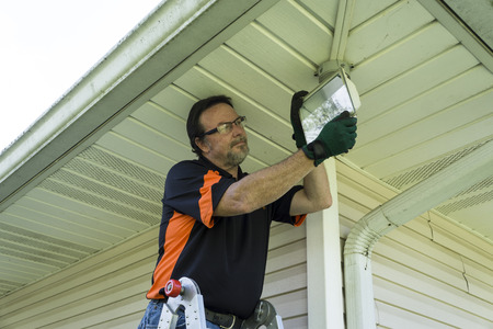 Electrician changing a bulb in a outside light fixture. Archivio Fotografico