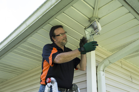 light worker: Electrician taking glass cover off outside light fixture to change light bulb.