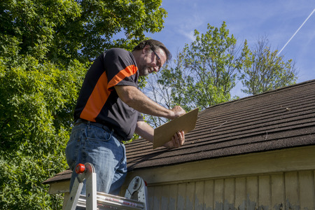 damaged roof: Contractor using a clipboard to figure our repiar cost for hail damaged roof. Stock Photo