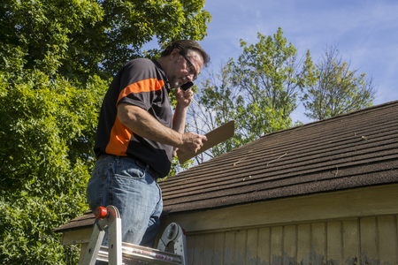Contractor on ladder with cell phone figuring out hail damage repair costs for customer. Archivio Fotografico