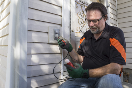 electrician tools: Electrician using a tester on a outside house outlet.