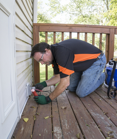 patio deck: Electrician testing outside outlet on patio deck. Stock Photo