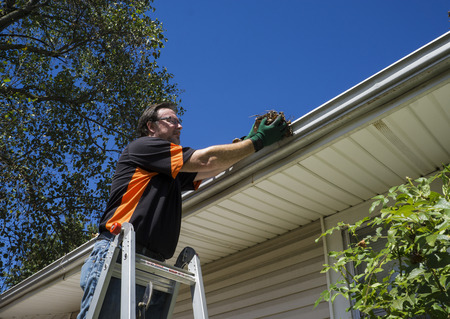 Worker cleaning gutters on a customers home. Archivio Fotografico