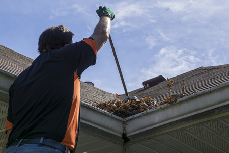 roofs: Worker sweeping leaves and sticks from a valley of a roof. Stock Photo