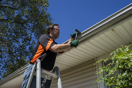 Worker repairing a gutter on a customers home.