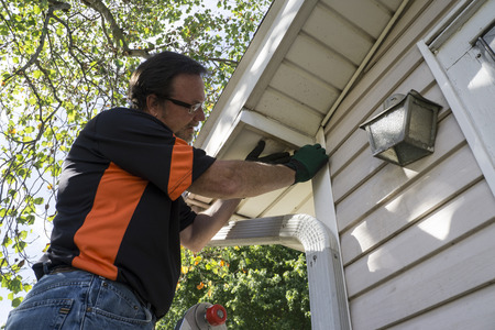 soffit cladding: Contractor fixing vinyl siding for customer.