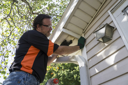 soffit cladding: Contractor popping vinyl siding back in place for a customer. Stock Photo