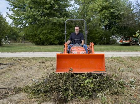 front loader: podador de árboles pisando fuerte hacia abajo pila rama de un árbol con el cargador frontal del tractor. Foto de archivo