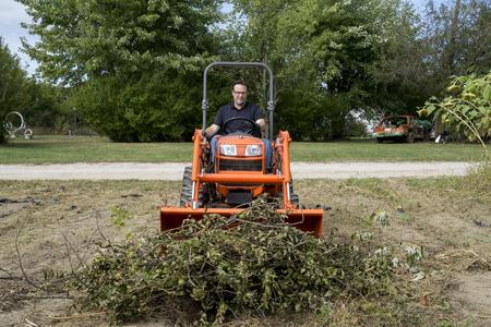 cargador frontal: Condensador de ajuste del árbol que empuja una pila de ramas de los árboles con el cargador frontal del tractor. Foto de archivo