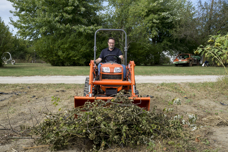 front loader: Tree trimmer pushing a pile of tree limbs with tractor front loader.