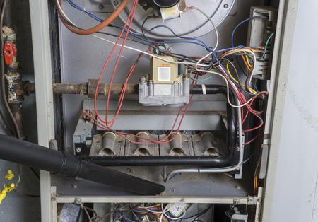 청소하는 동안 가스 용광로의 내부 진공 청소기 수리 공. 스톡 콘텐츠