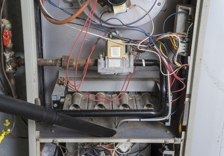 Repairman vacuuming inside of a gas furnace during a cleaning. Standard-Bild