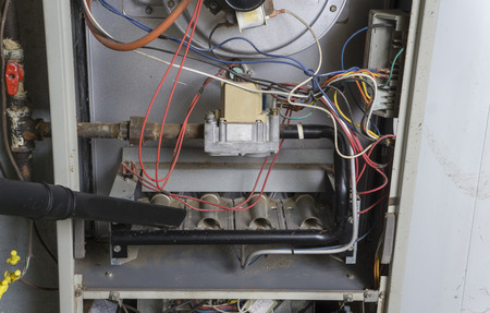 furnace: Repairman using a vacuum inside of a gas furnace.