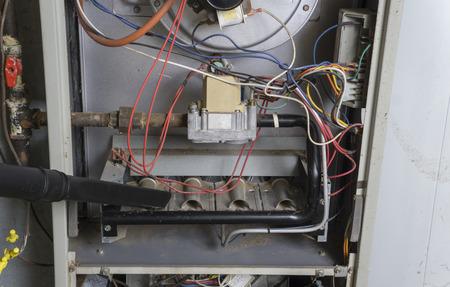 Repairman using a vacuum inside of a gas furnace.