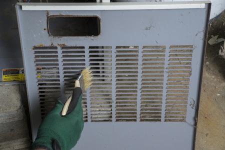 Techniker die vordere Abdeckung Reinigung OS ein Gasofen vor der Neuinstallation. Standard-Bild - 46562870
