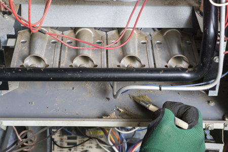 Technican using brush to clean under burners on a gas furnace. Standard-Bild