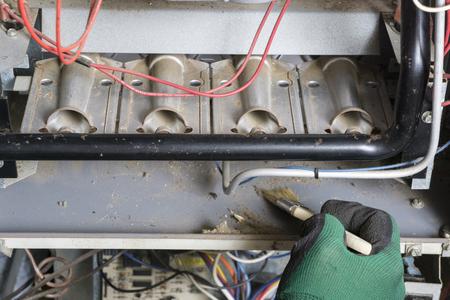 Technician은 가스로에서 버너 아래에서 브러시로 청소합니다.