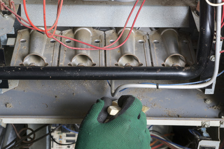 Technician cleaning a burner area of a natural gas furnance.