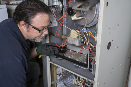and heating: Technician looking over a gas furnace with a flashlight before cleaning it.