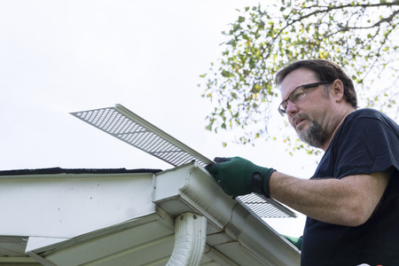 gutter: Handyman installing plastic gutter guards on a home.