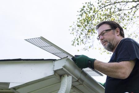 installer: Handyman installing plastic gutter guards on a home.