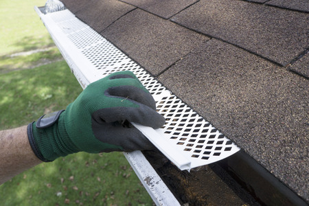 gutter: Contractor adjusting plastic gutter guards to get them to fit. Stock Photo