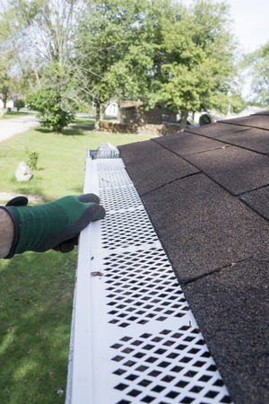 Contractor checking installation of plastic leaf guards on a customers gutter.