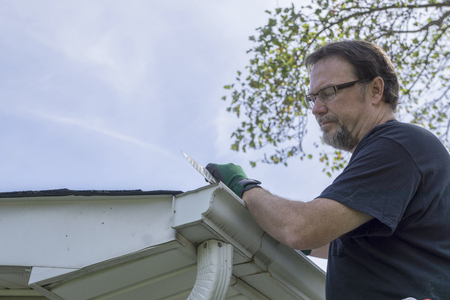 Contractor installing plastic gutter guards on a older home.