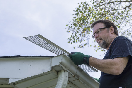 gutter: Contractor examing leaf guard before installing it on gutter. Stock Photo