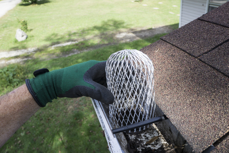 Contractor installing a down spout filter/strainer on a customers gutters. Archivio Fotografico