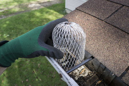Contractor installing a down spout filter on a residential home.