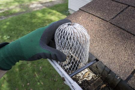 Auftragnehmer einen nach unten Tüllensieb auf einem Wohnhaus zu installieren. Standard-Bild - 46860310