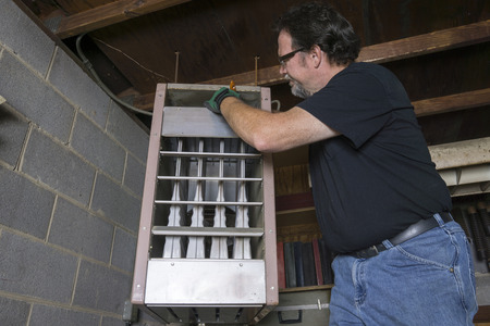 Repairman cleaning the upper duct of a overhead gas heater.