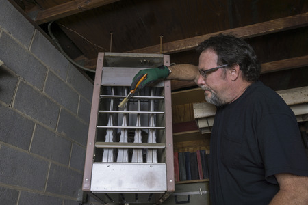 grates: Repairman cleaning the grates of a over head gas furnace.