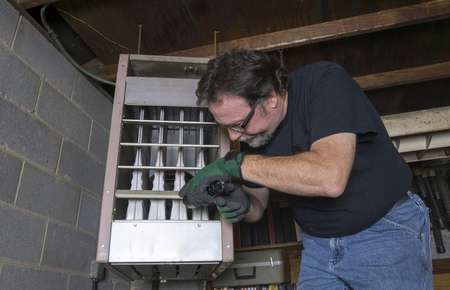 Technician checking out a overhead gas furnace in a commercial building. Standard-Bild