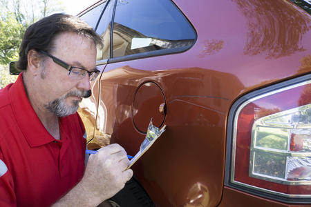 Insurance adjuster figuring damages done to a customers vehicle. Stock Photo