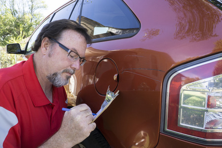 estimating: Insurance adjuster estimating dames done to a vehicle.