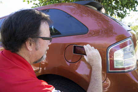 adjuster: Insurance adjuster taking photos of damage done to a insureds car.