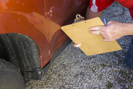 adjuster: Insurance adjuster examining damage done to bottom of vehicle.