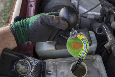 antifreeze: Mechanic checking strength of antifreeze with a guage.