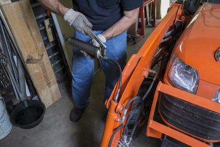 Mechanic using a grease gun to lube a tractor. Фото со стока