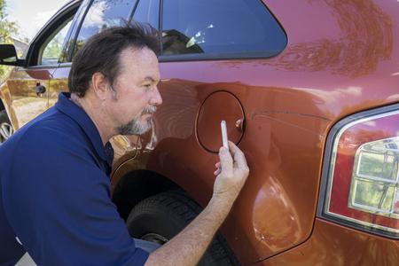 adjuster: Adjuster taking photos of damage to insureds vehicle.
