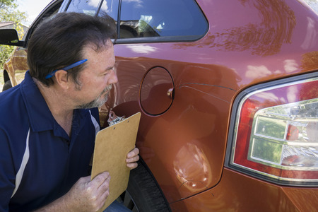 adjuster: Adjuster looking at damage on a insureds vehicle. Stock Photo